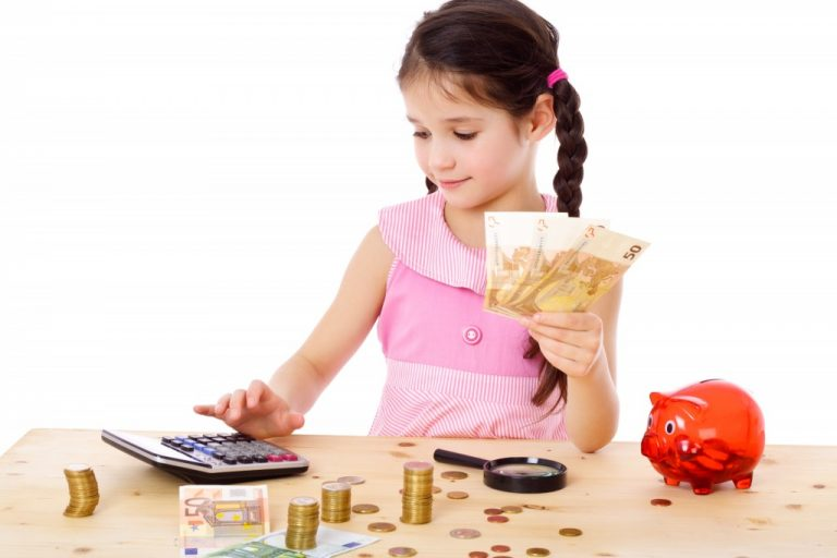 young girl holdin euros and calculating something with money and a piggy bank on the table in front of her
